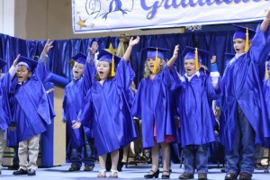 "Kinder grads on stage singing ""I'm a Huckabay kid, I don't want to grow up."""