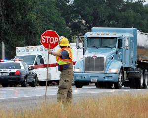A rescue worker signals for traffic to slow down as vehicles pass the accident scene.