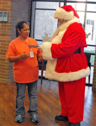 Santa delivering the surprise donation to Maria Tovar. || Flash photo by DAVID SWEARINGEN