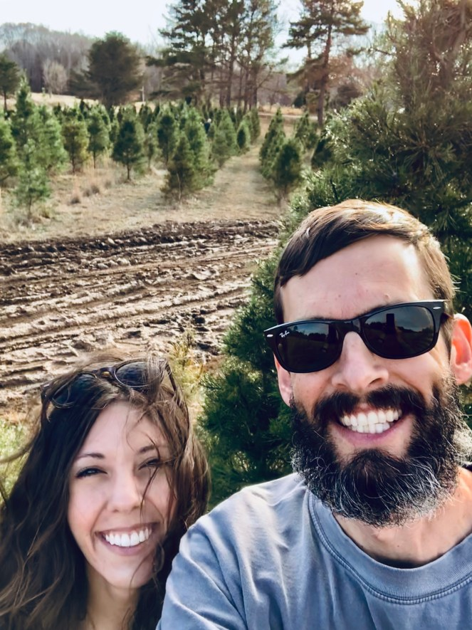 smiling happy married couple love christmas tree farm