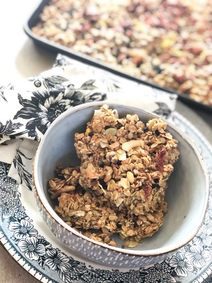 Two bars of granola in a grey bowl on a blue and white plate with a silver charger. You can see the pan of granola in the background and a flowered black and white cloth napkin frames the bowl.