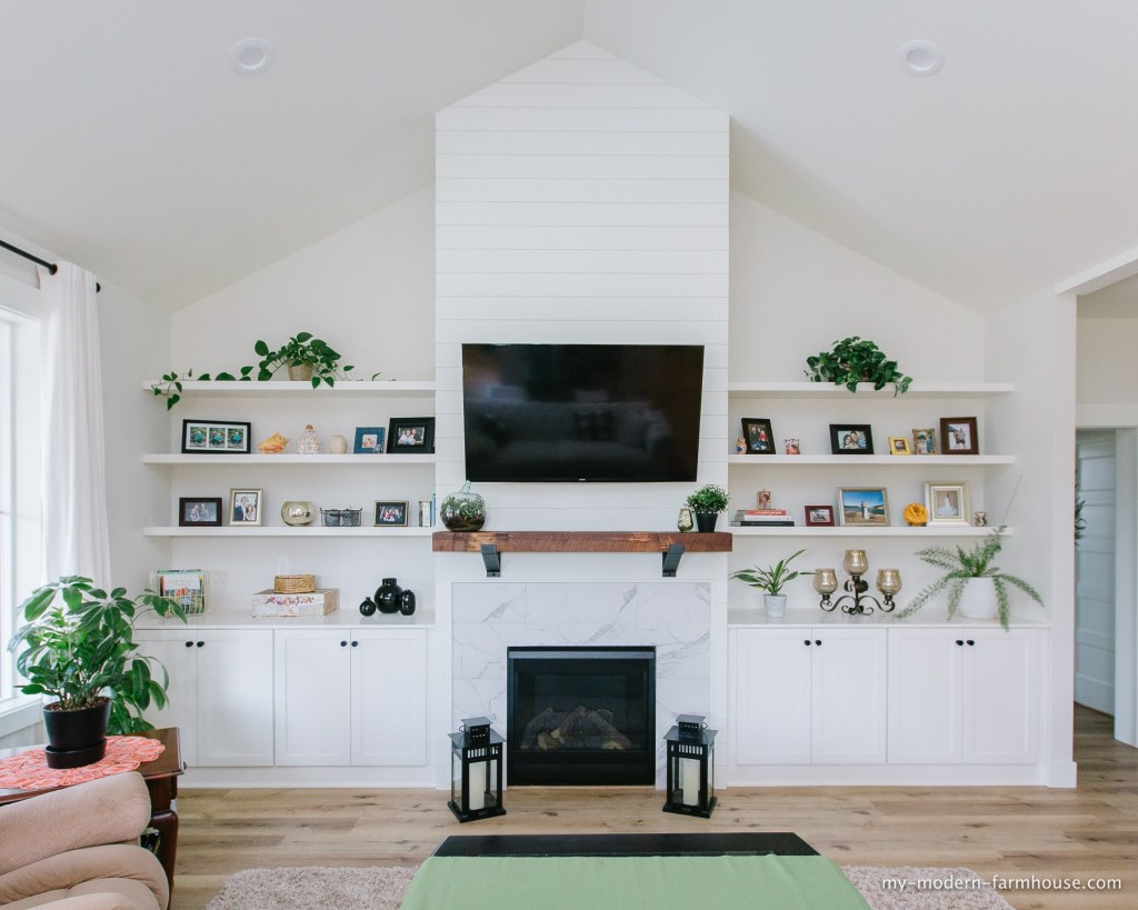 modern farmhouse living room with built in shelving, reclaimed wood mantle, and shiplap fireplace