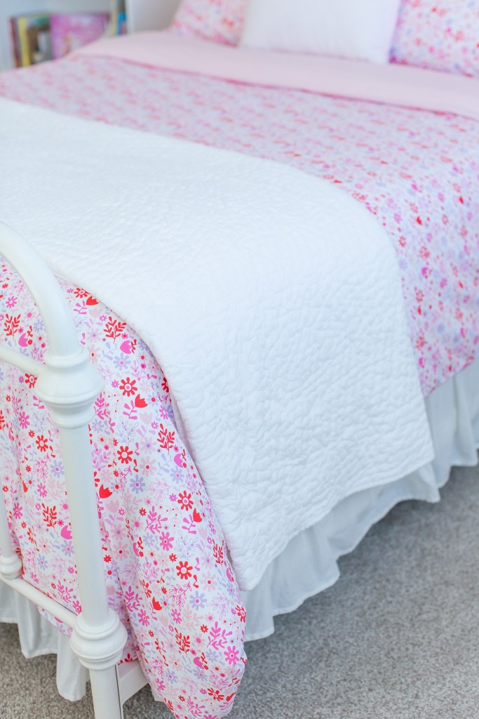 Close-up of white coverlet on pink floral bedding