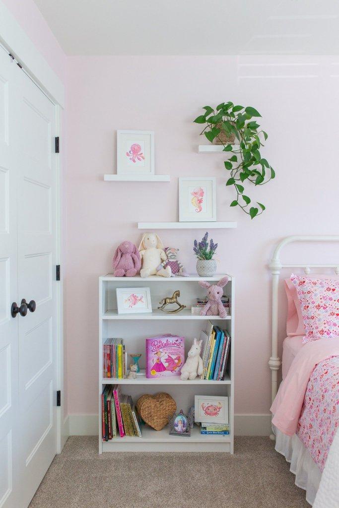 Pink bedroom with white bookshelf