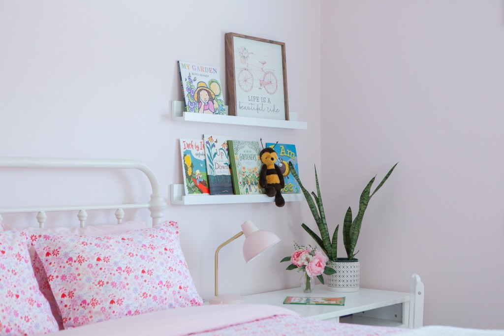 children's garden books on shelf in pink floral bedroom
