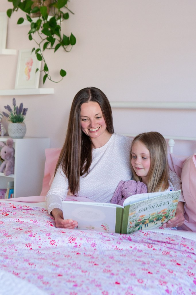 mommy and daughter reading garden book in pink floral bedding
