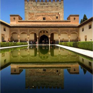 Alhambra with blue skies reflected on still water