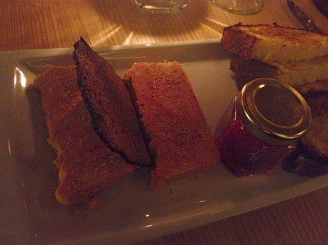 Plate of foie gras with gingerbread crisp, bread, and jar of preserves