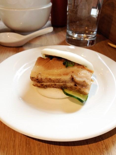 Steamed pork fun on a white plate at a restaurant.