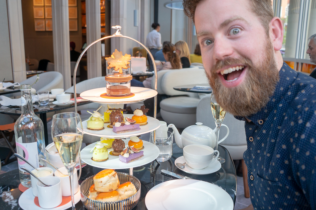 Adam sitting in front of our spread at The Connaught Afternoon Tea the seventh blogiversary
