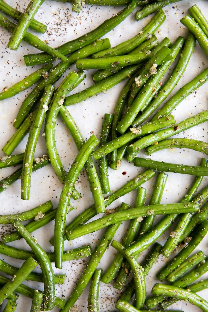 Green beans tossed in olive oil, salt, and garlic spread over a large baking sheet covered with parchment paper.