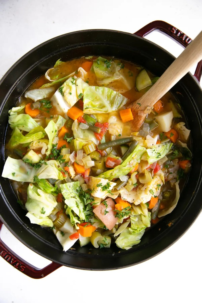 Large pot filled with homemade vegetable soup filled with cabbage, potatoes carrots, celery, and zucchini.