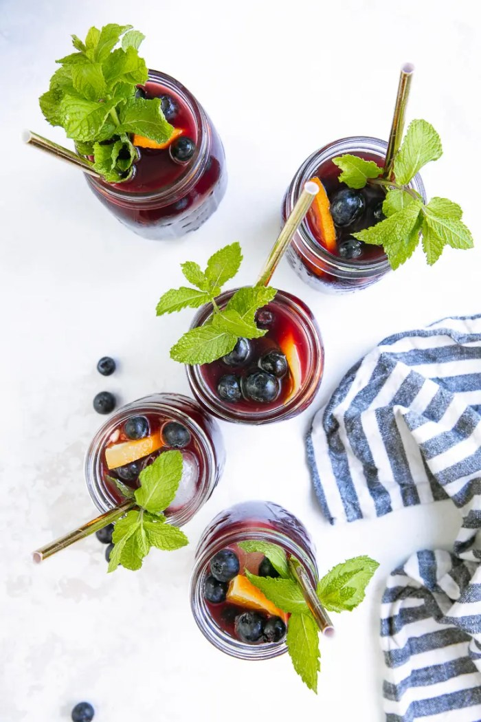 Flat-lay image of five glasses filled with Blueberry Sangria and garnished with mint