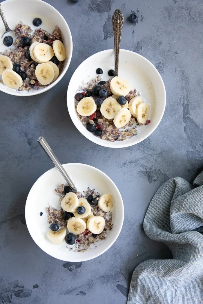 Overhead view of homemade instant oatmeal with milk and fresh fruit in white serving bowls