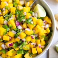 Overhead image of a large white bowl filled with mango salsa made with mango, red onion, cilantro, and lime juice.