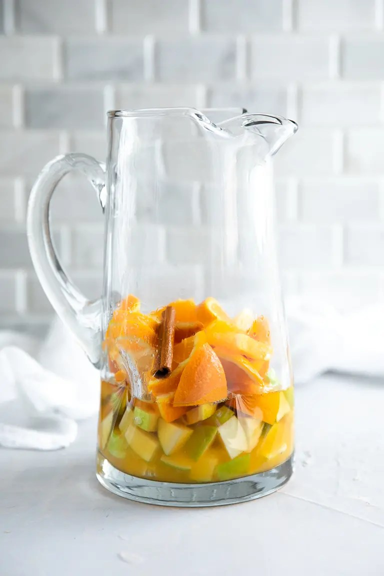 Glass pitcher filled with sliced oranges, lemons, chopped Granny Smith apples, orange juice, and brandy.