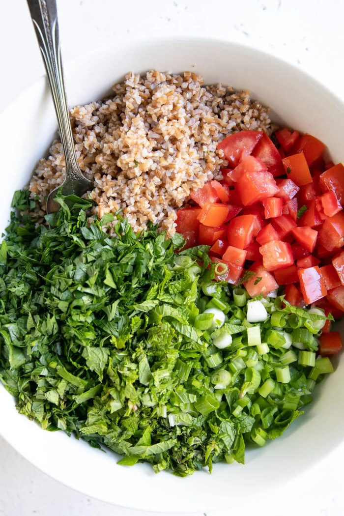White salad bowl filled with cooked bulger, chopped tomatoes, green onion, mint, and parsley.
