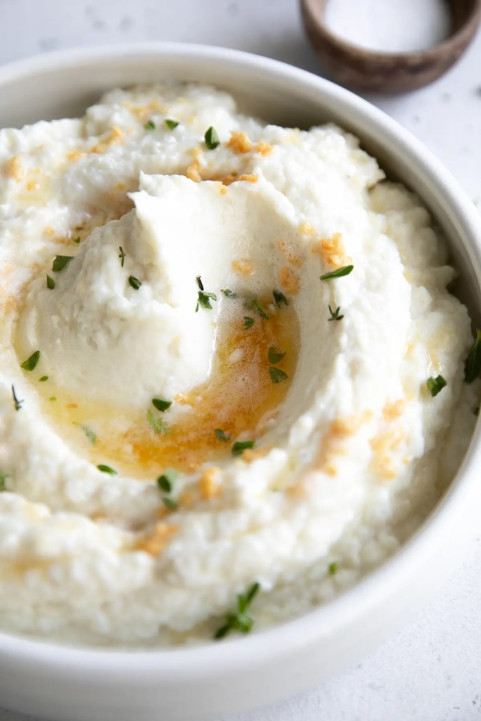 White serving bowl filled with creamy mashed cauliflower drizzled with brown butter and garlic.