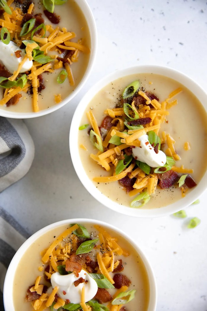 Three white bowls filled with creamy potato soup and topped with green onions, sour cream, cheddar cheese, and bacon.