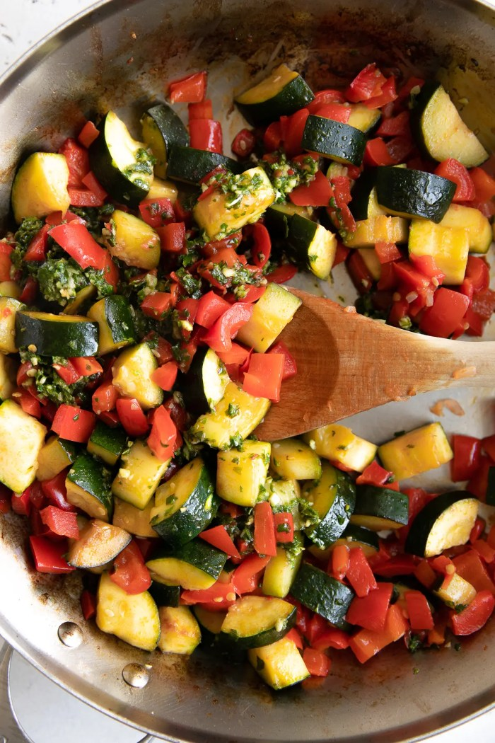Zucchini and bell peppers mixing with homemade pestata in a large stainless steel skillet.