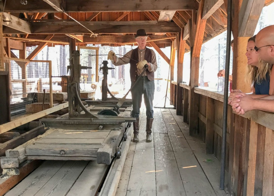 Docent In Period Costume Demonstrating Lumber Mill