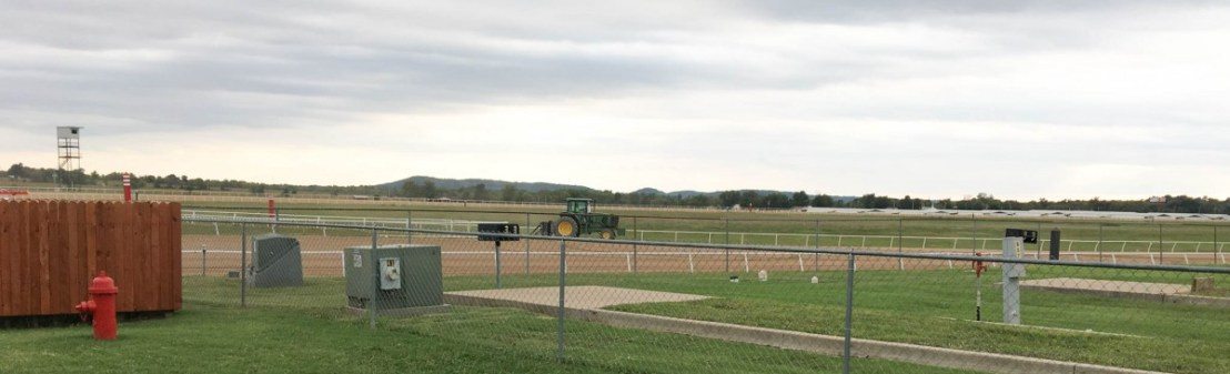 Workers Grooming Racetrack Seen From Dog Park