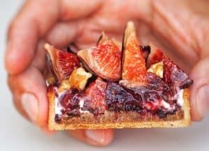 Tartelette figue et noix coupée et tenue dans une main