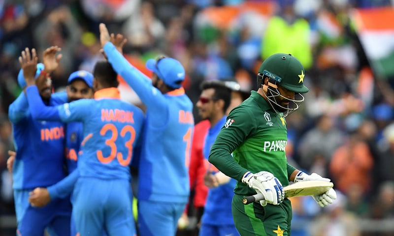 TOPSHOT - Pakistan's Mohammad Hafeez (R) walks back to the pavilion after his dismissal during the 2019 Cricket World Cup group stage match between India and Pakistan at Old Trafford in Manchester, northwest England, on June 16, 2019. (Photo by Dibyangshu SARKAR / AFP) / RESTRICTED TO EDITORIAL USE