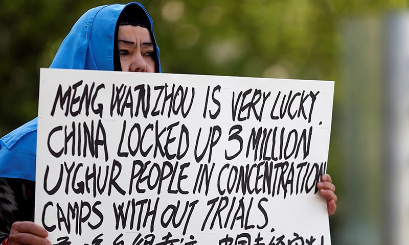FILE PHOTO: Dilibair Yusuf holds a sign protesting China's treatment of Uighur people in the Xinjiang region during a court appearance by Huawei's Financial Chief Meng Wanzhou, outside of British Columbia Supreme Court building in Vancouver, British Columbia, Canada, May 8, 2019. REUTERS/Lindsey Wasson/File Photo