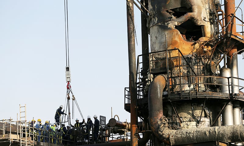 FILE PHOTO: Workers are seen at the damaged site of Saudi Aramco oil facility in Abqaiq, Saudi Arabia, September 20, 2019. REUTERS/Hamad l Mohammed/File Photo