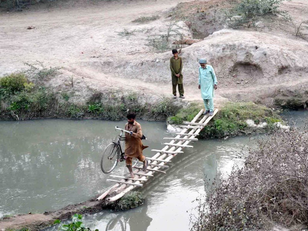 Pic29-001 CHINIOT: Nov29- People crossing a temporary wooden bridge as due to lack of permanent bridge on Jhang Road area, needs the attention of concerned authorities. ONLINE PHOTO by Malik Muhammad Ali