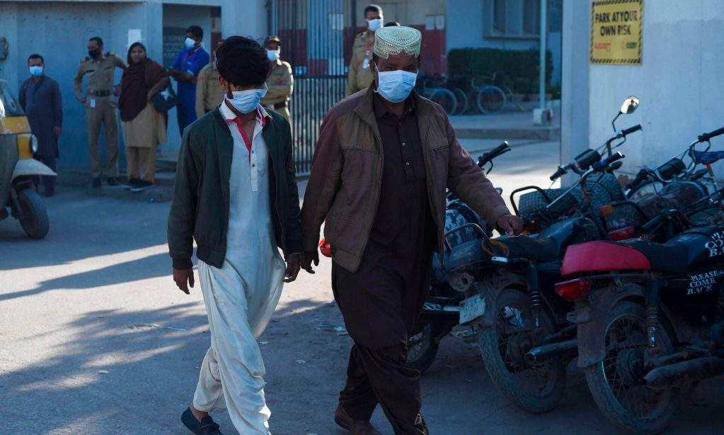 Peoples wearing facemasks walk past outside an hospital entrance in Karachi on February 17, 2020, after agasleakkilledfive people and sickened dozens of others in a coastal residential area in Pakistan's port city ofKarachi. (Photo by Rizwan TABASSUM / AFP)