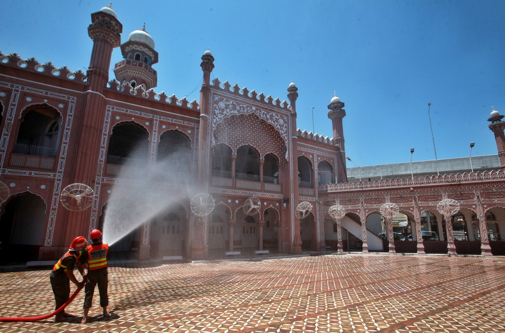 PESHAWAR Staffers of Rescue 1122 doing disinfectant spray at Sunehri Masjid as preparation for Jumat ul Wida. — Photo by Ghulam Murtaza