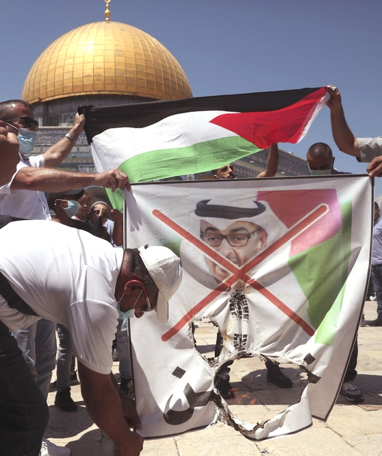 Palestinian protesters burn a banner showing Abu Dhabi Crown Prince Mohamed bin Zayed al-Nahyan near the Dome of the Rock Mosque in the Al Aqsa Mosque compound in Jerusalem's old city, Friday, Aug. 14, 2020. (AP Photo/Mahmoud Illean)