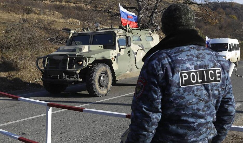 Russian peacekeeper vehicles drive through an ethnic Armenian checkpoint near Getovan in the separatist region of Nagorno-Karabakh several kilometers before the new border with Kalbajar district turned over to Azerbaijan, Wednesday, Nov. 25, 2020. The Azerbaijani army has entered the Kalbajar region, one more territory ceded by Armenian forces in a truce that ended deadly fighting over the separatist territory of Nagorno-Karabakh, Azerbaijan's Defense Ministry said Wednesday. The cease-fire, brokered by Russia two weeks ago, stipulated that Armenia hand over control to Azerbaijan of some areas its holds outside Nagorno-Karabakh's borders. (AP Photo/Sergei Grits)