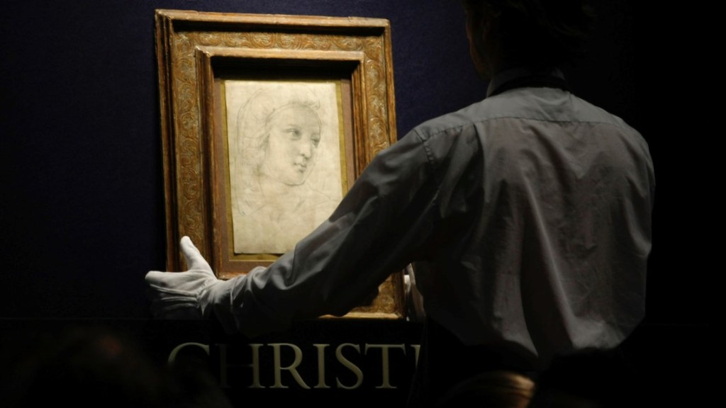 A Christie's employee removes the Raphael painting 'Head of a muse' after it was sold in the 'Old Masters and 19th Century Art' auction held at their premises in London, Tuesday, Dec. 8, 2009. The painting fetched 26 million pounds (US$42,744,000; euro 28,704,000) and 29.2 millions pounds including fees, a record price for any old master drawing. (AP Photo/Matt Dunham)