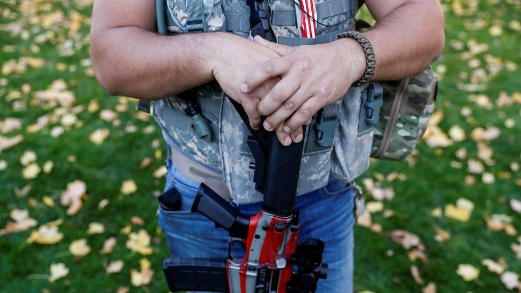 FILE PHOTO: A member of Michigan Liberty Militia stands with a gun while supporters of U.S. President Donald Trump rally outside the State Capitol building as votes continue to be counted following the 2020 U.S. presidential election, in Lansing, Michigan, U.S., November 7, 2020. REUTERS/Shannon Stapleton/File Photo