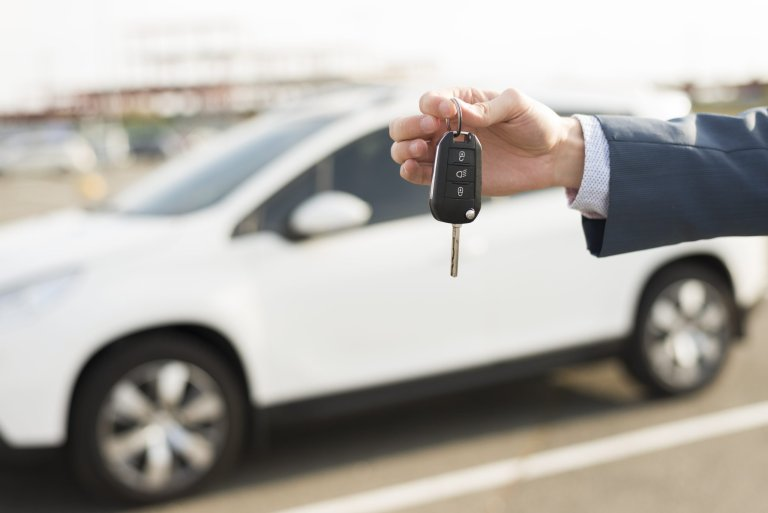businessman-with-keys-front-car