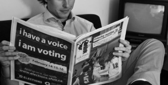 Student reading an issue of the Fulcrum newspaper