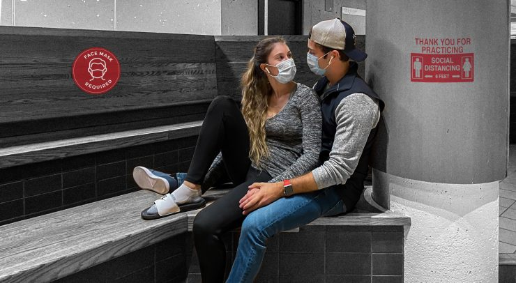 Two people with masks sitting together romantically
