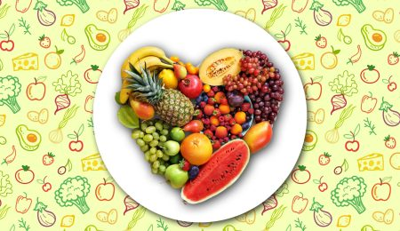 A plate of vegetables and fruits forming a heart