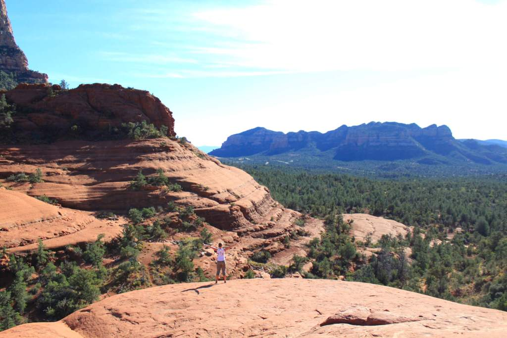Gwen with arms spread wide in front of red rock formations and pine forest in the Southwest