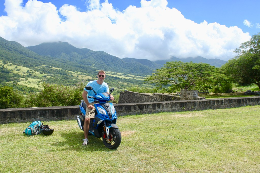 M on a scooter with the green mountains of St. Kitts in the background - the perfect St. Kitts  DIY shore excursion!
