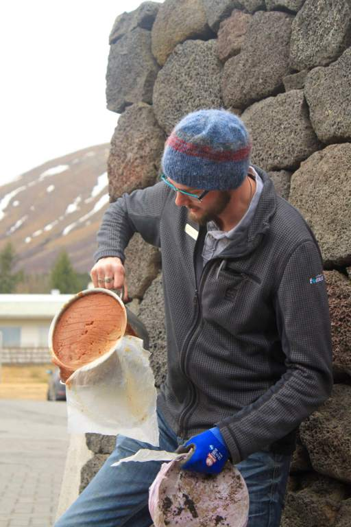 Snorri revealing bread that had been baked in a ceramic pot underground.