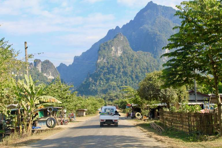 Truck on rural Laotian road with mountains beyond