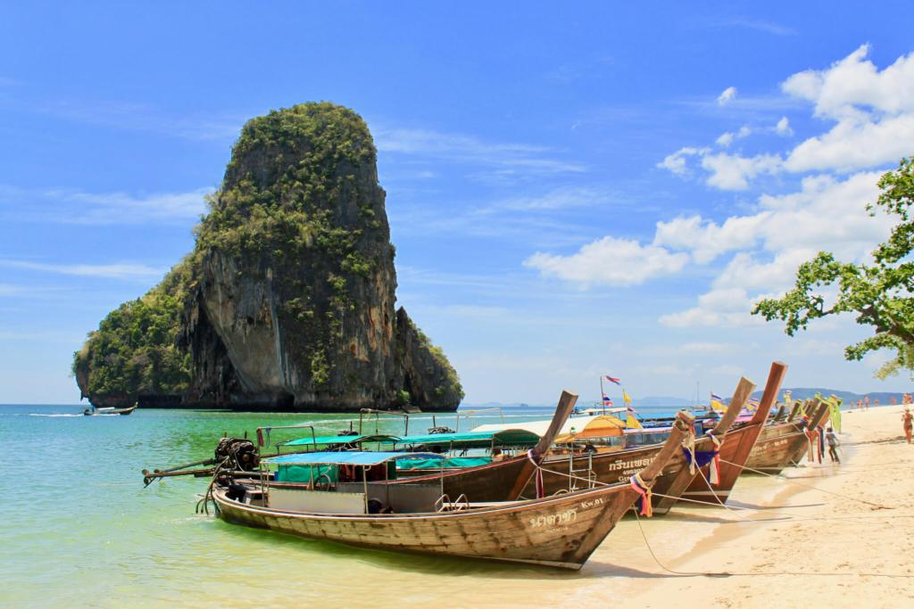 Thai longboats in a gorgeous sea in front of a karst mountain