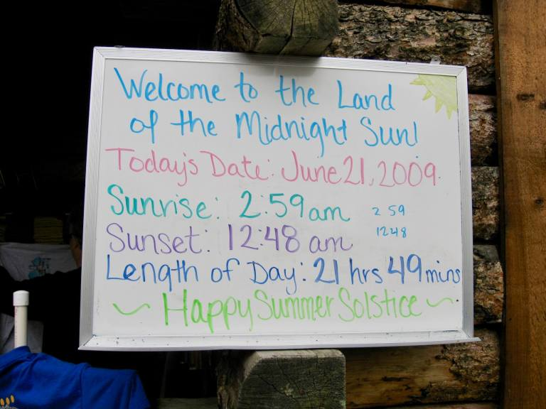 Solstice sign stating a 2:59 AM sunrise and 12:48 AM sunset. Add some sleeping aids to your Alaska packing list to help combat all that midnight sun.