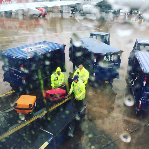Men unloading luggage from plane