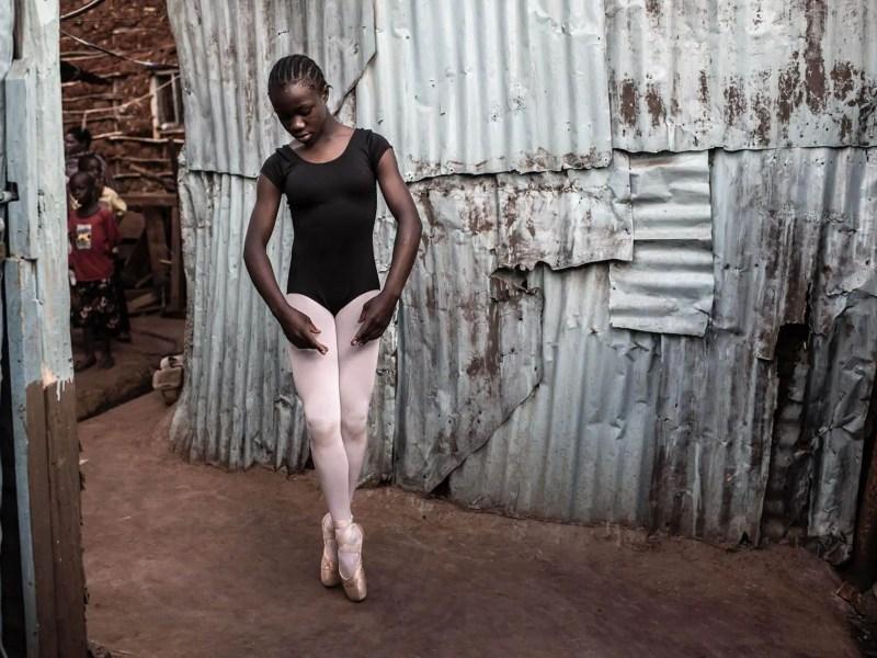 A young ballerina next to a tin shack