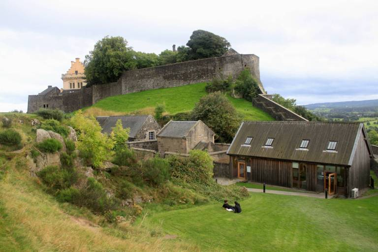 Green, hilly section of Stirling Castle complex